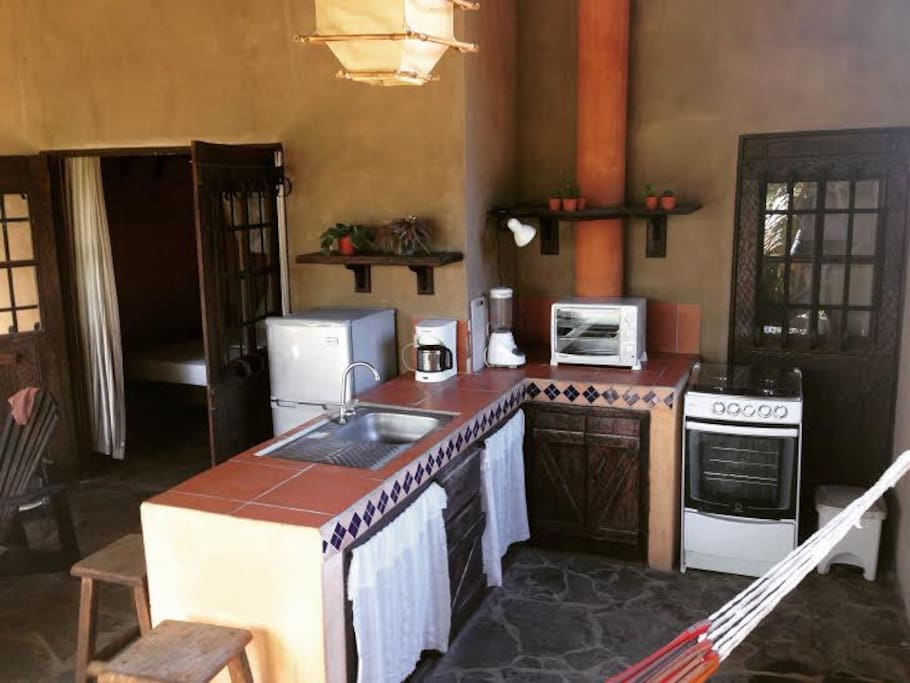 Kitchen with fridge/freezer, gas stove/oven, electric toaster oven, coffee maker and blender.
