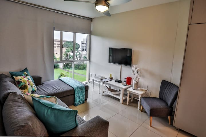 Living area with satellite tv and wifi with beautiful view over the garden and play area and the ocean