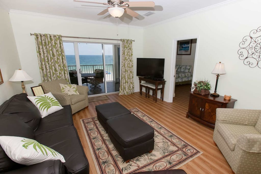 Living room with flat screen TV and sliding glass doors to Gulf-front balcony