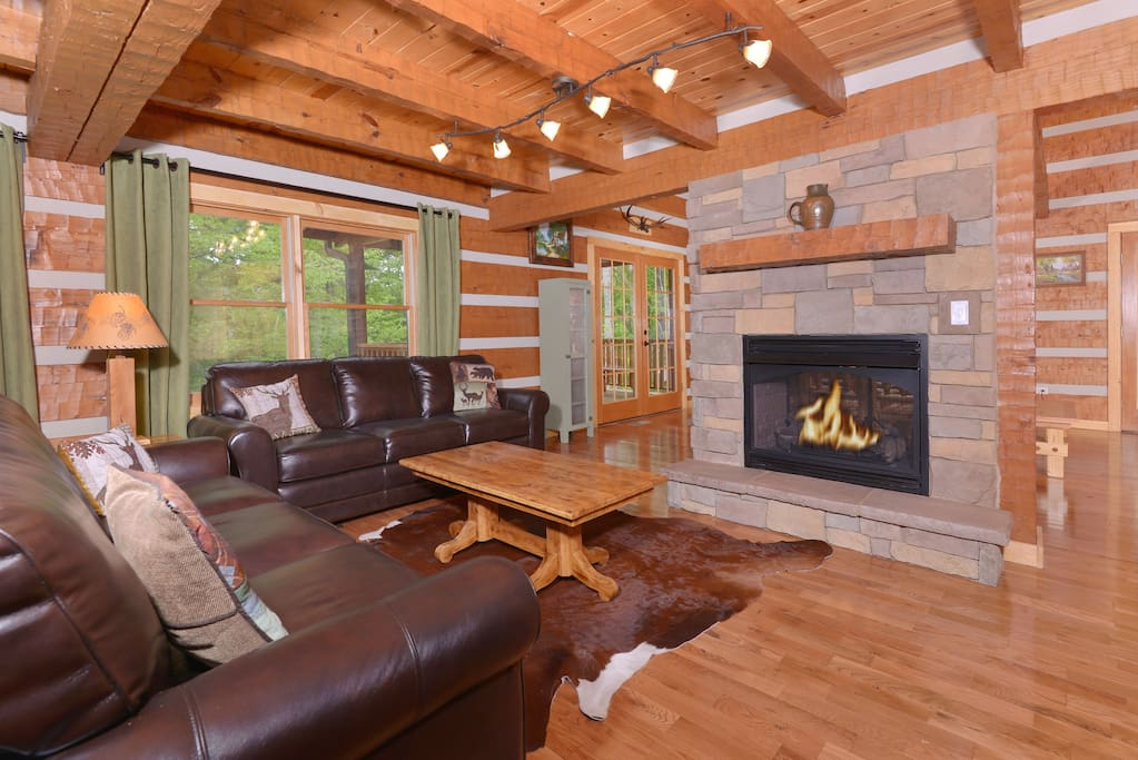 Fireplace opens to inviting living room with leather furniture