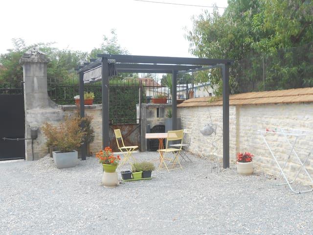 Petit salon de jardin avec pergola vers lequel on peut garer sa voiture.