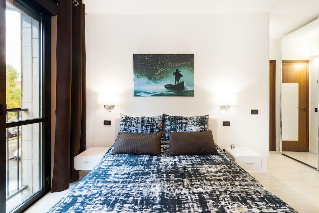Foto verificata air BnB spaziosissima camera da letto con grande finestra affacciata sul parco davanti all' appartamento.tende oscuranti danno anche un tocco elegante alla stanza