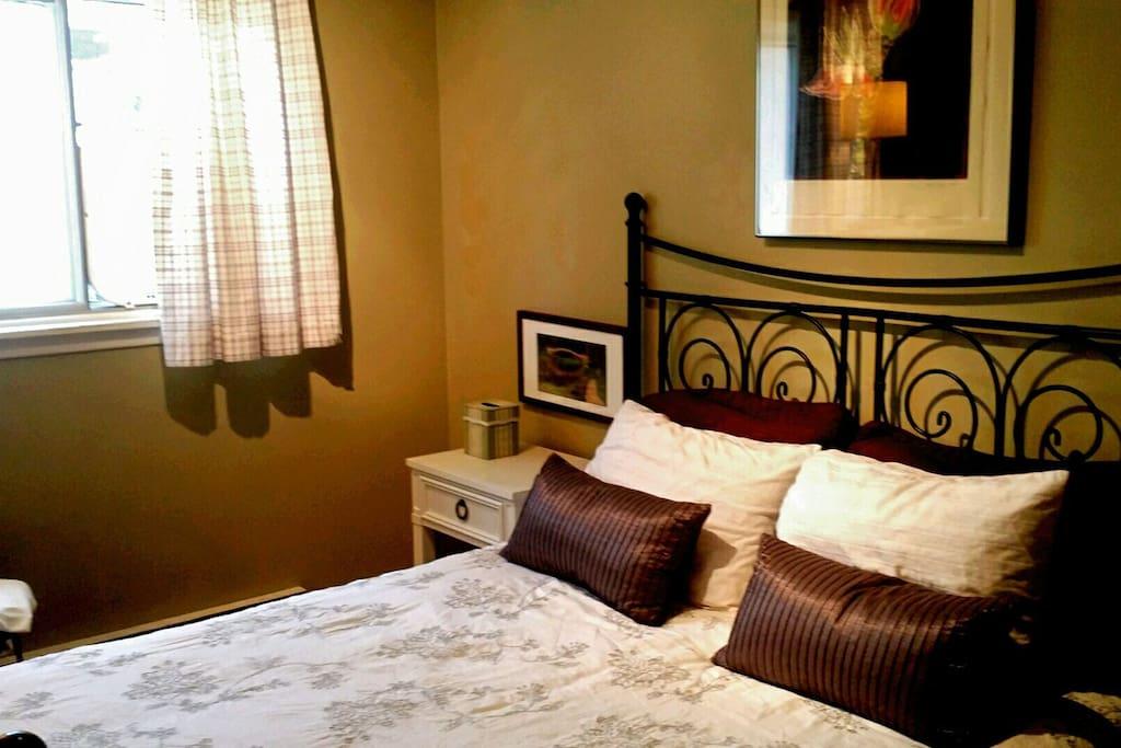 Bedside table, dresser, closet, storage, hangers, TV, window fan, and laundry basket.