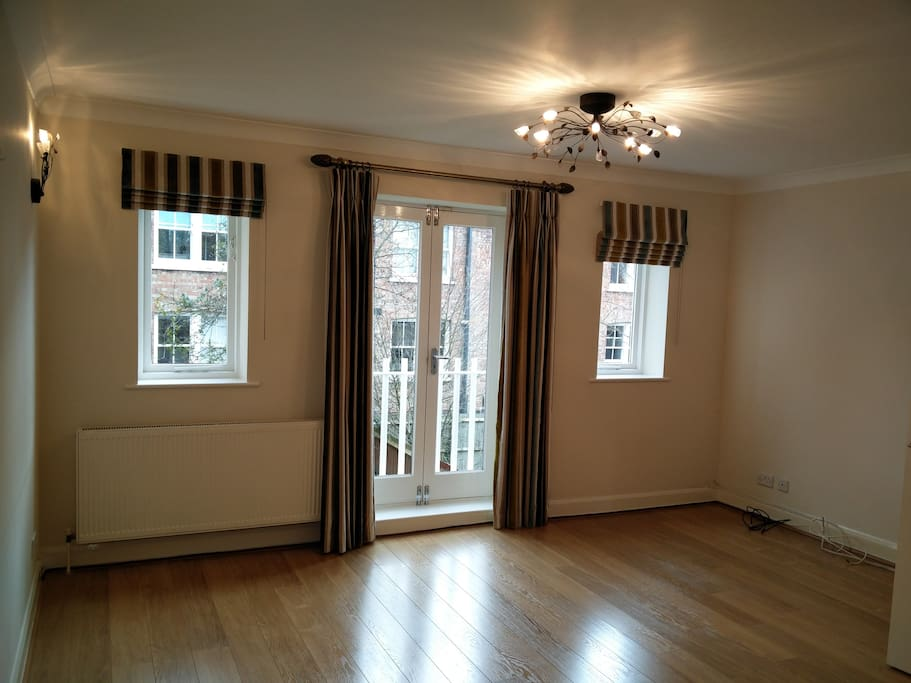 Large living space with gorgeous curtains and new wooden floor