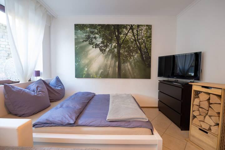 Bequemes Doppelbett im Wohn/Schlafzimmer mit Flachbildfernseher daneben der Holzvorrat für den gemütlichen Kamin.