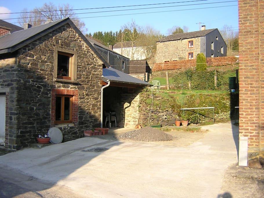 La cour entre la maison et le fournil et le jardin en arrière plan.