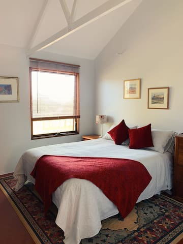 Main Bedroom with queen bed, linen sheets and a view without having to get out of bed.