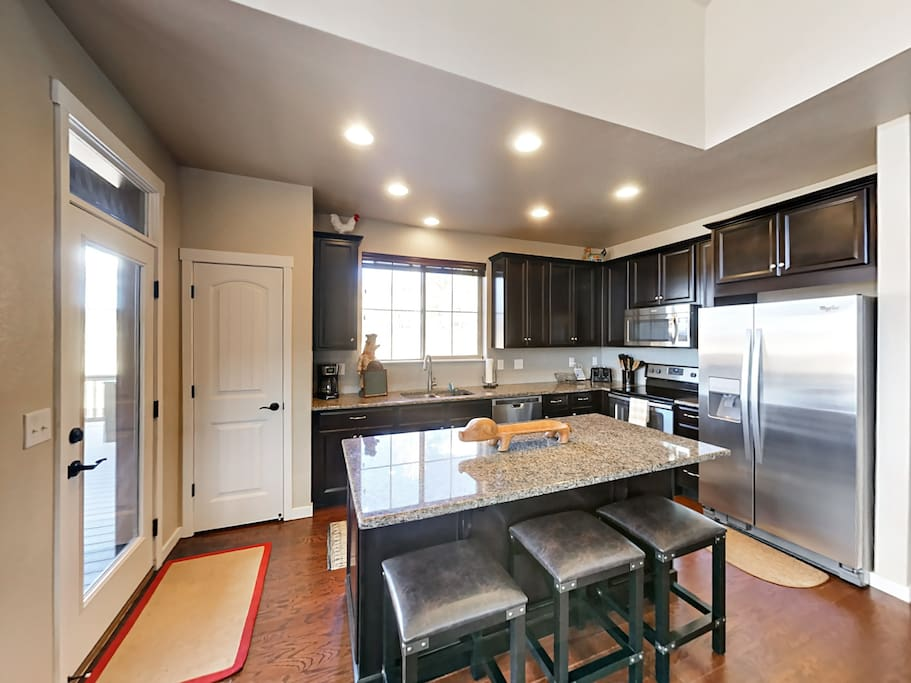 This gleaming granite kitchen has an island with bar seating for 3.