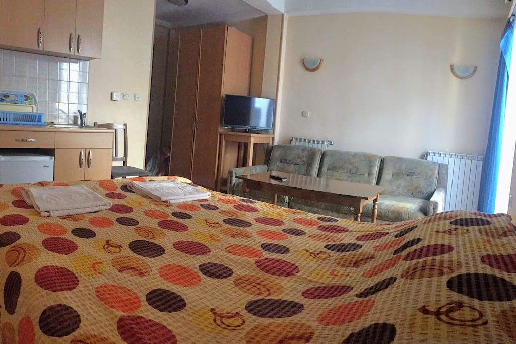 The room has couch, small table, TV and wardrobe