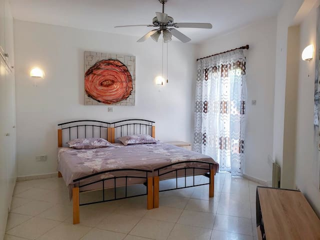 Large bedroom with one king-size bed, air conditioning, heating, and ceiling fan