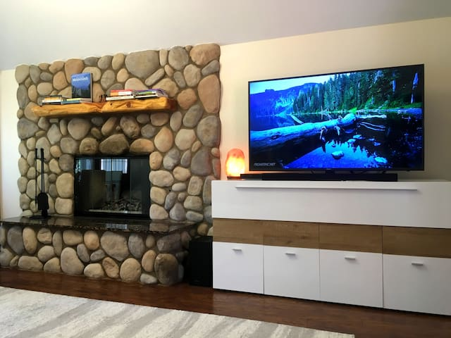 """Contemporary living room featuring a stone accent fireplace and 55"""" home theater with Dolby sound, all facing you sitting on the leather sofa."""