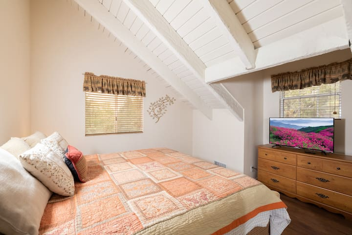Upstairs bedroom with King bed, TV with Netflix, and bedside lamp with USB ports for easy phone charging.