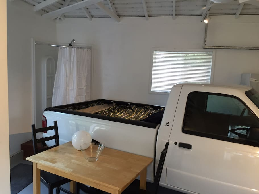 A unique comfortable full size memory foam 'double bed' in the truck-bed of an electric Ford Ranger EV (non-operational), corner shower stall, table/desktop and chairs