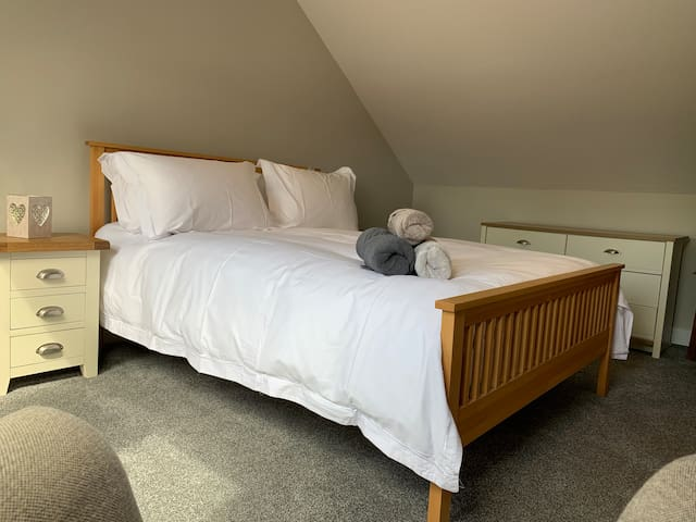 Upstairs king size bedroom with comfortable mattress, luxury linen, plenty of drawer storage and Sky TV