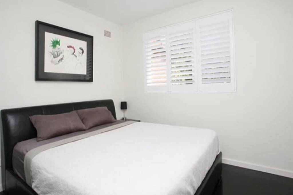 Double bedroom with large window and slide robes. The Modern look and feel runs throughout the apartment.