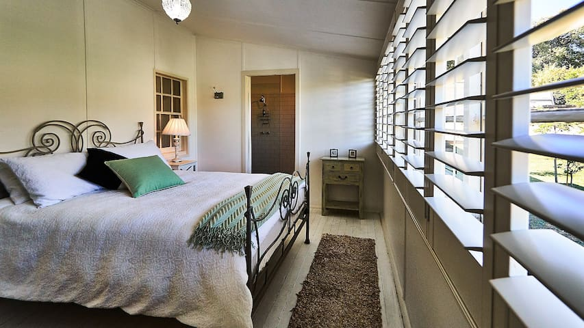 Our sunny bedroom overlooking a stand of roses and tree gardenias. Bed is super comfortable with quality linen