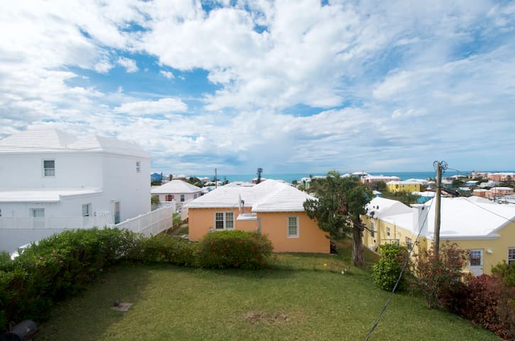 """From the second story window you get a great view of the back garden, Bermuda's pastel homes, and the Atlantic Ocean.  If you look carefully, those blurry patches above the orange house are rain falling in the distance.  It was a typical Bermuda day, torrential """"Tank"""" rain followed by the most Bermudiful day literally 10 minutes after"""
