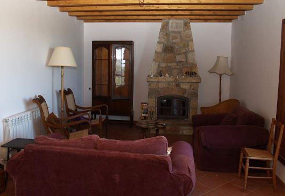 Cosy living room with woodburning stove and ample comfortable seating including a bed settee.  Beautiful views of the mountains from the french doors