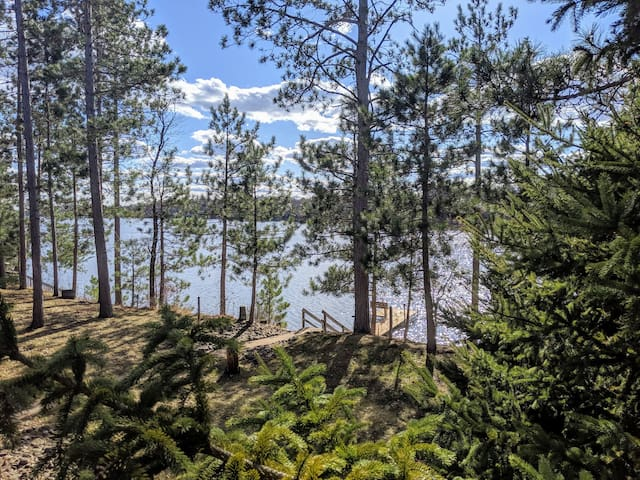 View from the upper deck of Long Lake, located in Burnett County, WI. Backyard is tree-lined along the perimeter with a balance of open space for outdoor activities. Watch for slightly uneven ground and tree stumps - we support natural terrain here!
