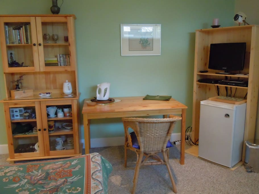 Convenience area with small fridge, TV, electric kettle and some dishes