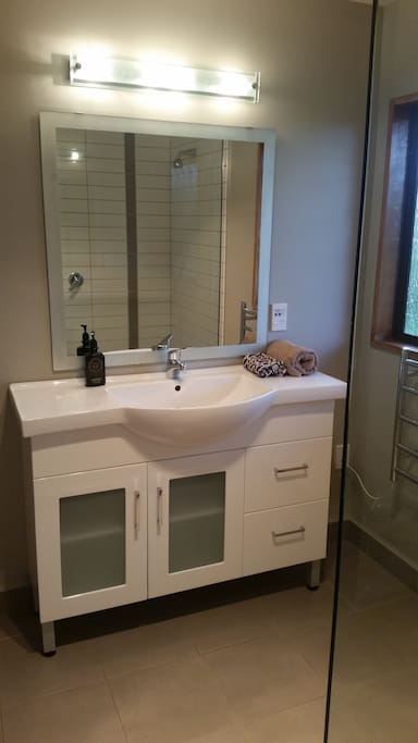 Large vanity, mirror with heat lamps and fan.