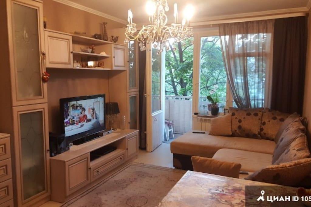Гостиная с двуспальным диваном и балконом в тихий зелёный двор