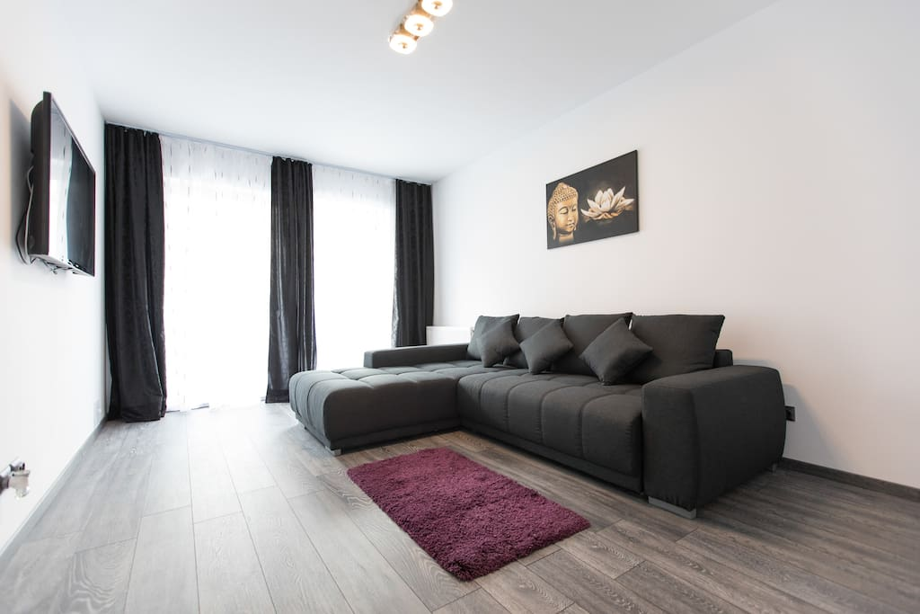 Living Room with large sofa that can turn into bed for 2 persons