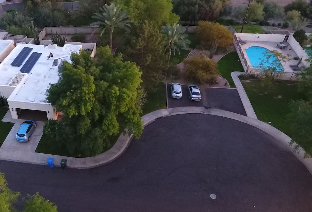 Another drone view showing the house, park, and pool