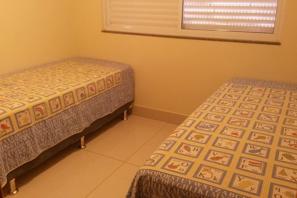 Quarto com duas camas de solteiro que podem ser juntadas e virar uma de casal.