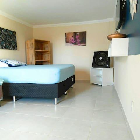 O quarto/sala, possui uma cama queen, uma de solteiro e um colchão adicional.