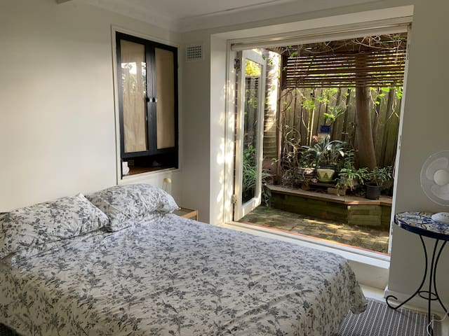 The bedroom has double glass doors that opne to a lush side garden and relaxing sitting area