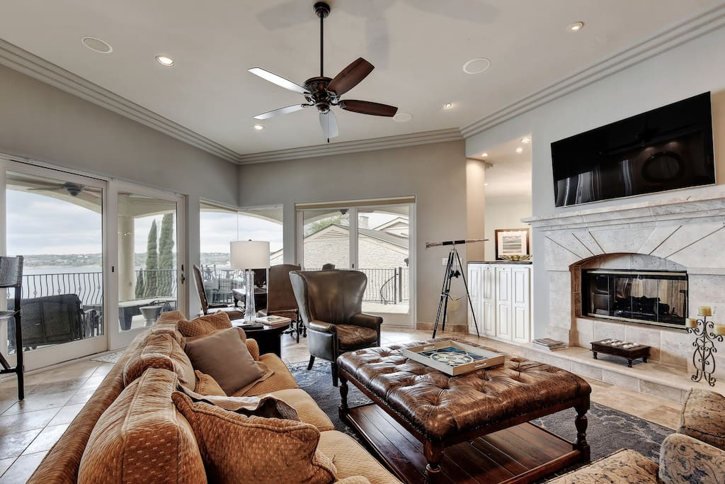 """The bright living room offers a 65"""" Samsung TV mounted above the fireplace"""