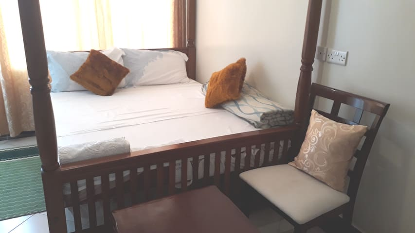 Bedroom with a double bed and clean beddings an extra small mattress is provided incase you want to relax on the balcony