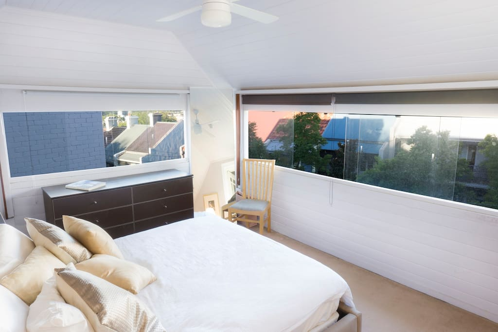 Enjoy this luxurious and stylish master bedroom with panoramic windows that can be shaded or left open to allow in the abundant natural light.