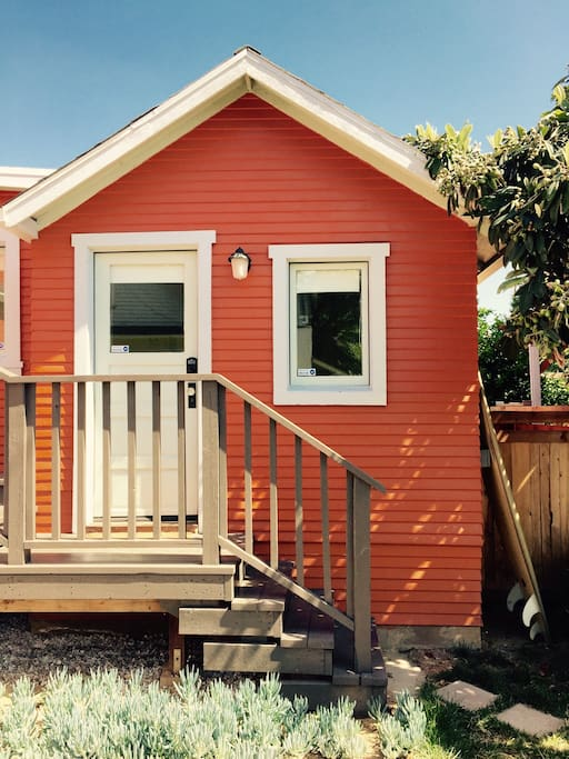 Tangerine-colored exterior of cottage with PRIVATE ENTRY. So cute!
