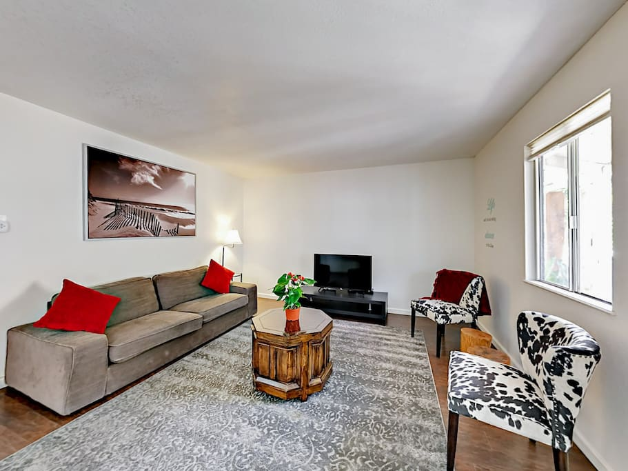 """The spacious living room has seating for 4 and a 44"""" flat-screen TV."""