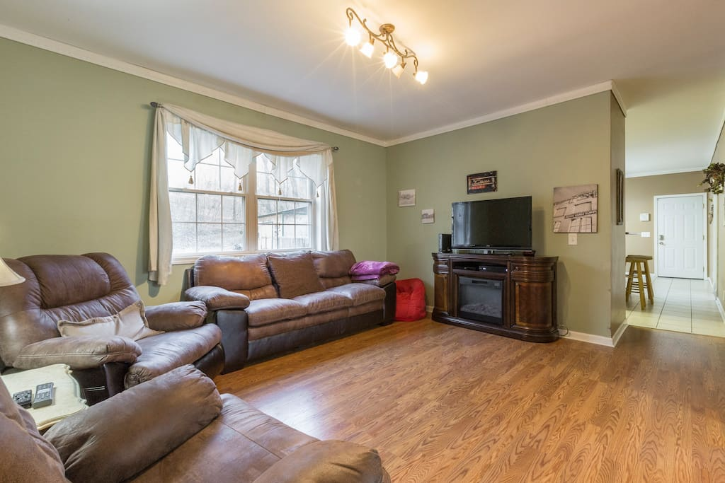 Six can sit comfortable in this sunny living room with hardwood floors and flat-screen TV.