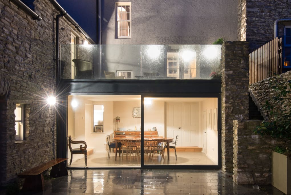 The back of the house shows that it has 4 levels. The basement level houses the cinema room which has a large double sofa bed so can be used as a 4th bedroom.  A clever extension has provided a large dining space and terrace above.  The yard is shared with the adjoining cottage.