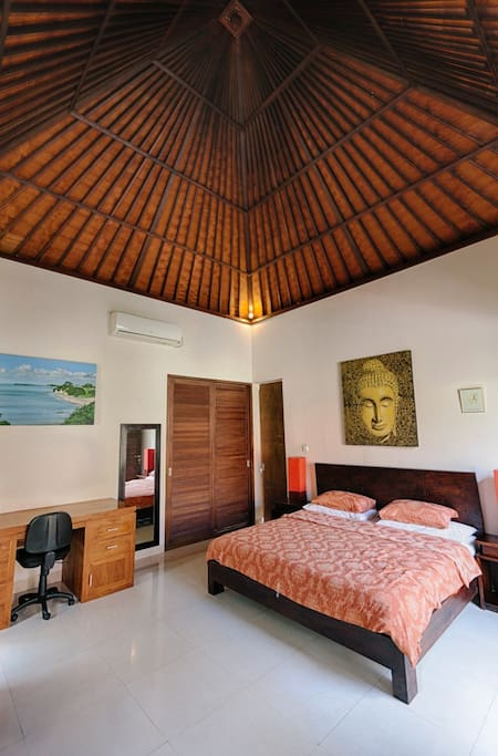 Balinese style bedroom with high ceiling.