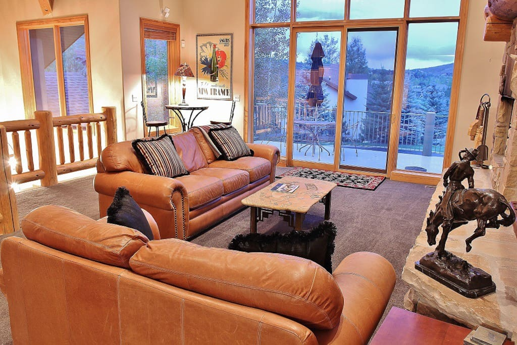 Living room with stone fireplace, lots of seating and private deck - Park City Tranquility - Park City