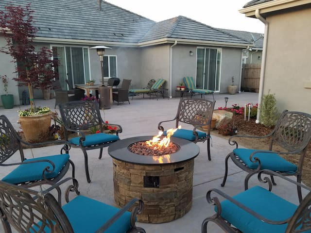 Outdoor terrace with several seating areas for dining and a fire pit for evening socializing