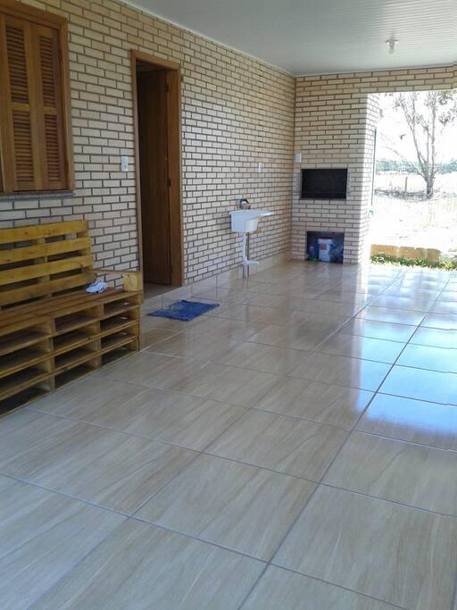 Garagem espaçosa e área de serviço com churrasqueira com acesso a área aberta nos fundos.