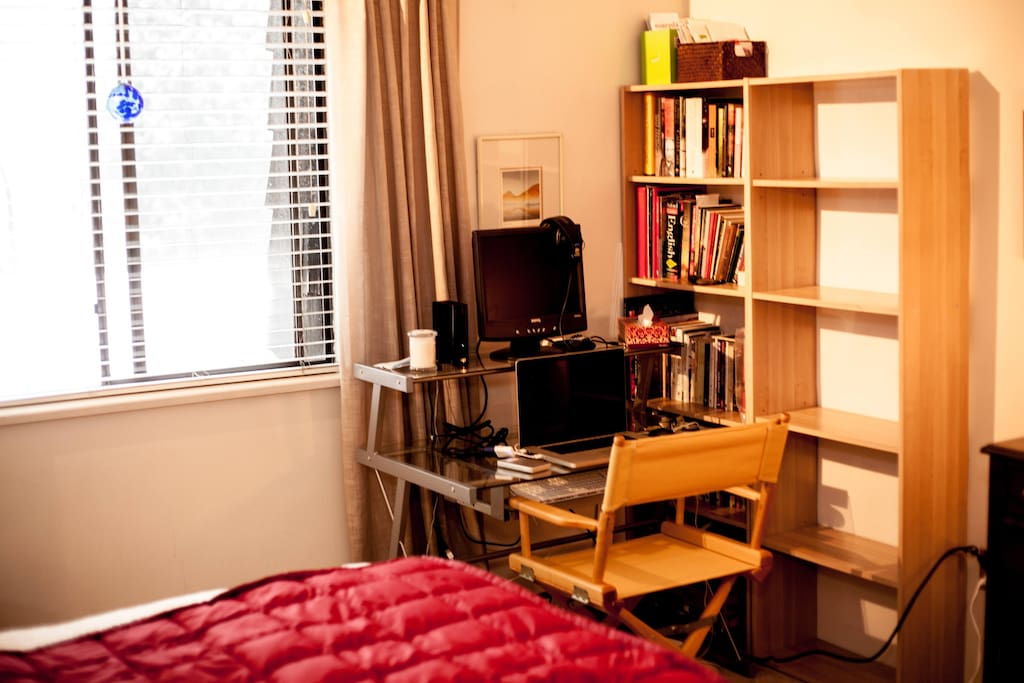 bookshelves and desk with big bright window with view of Lion's Gate bridge