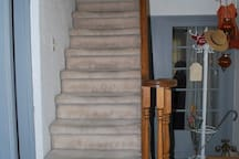 Steep stairway from front hall to upstairs suite.