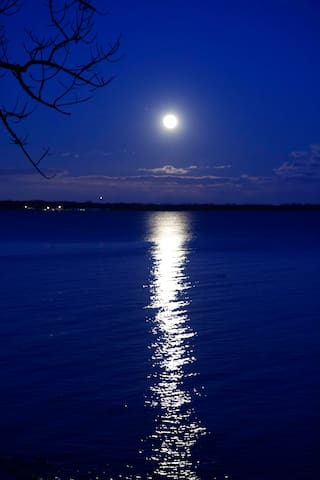 The moonlight shining over the water is a lovely sight from inside, on the deck, or on the beach with a campfire