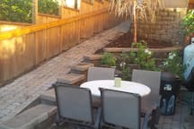 The courtyard has a four or more person outdoor table with a propane barbecue.