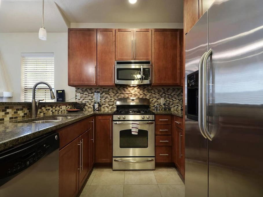 Updated kitchen with granite countertop and stainless steel appliances.