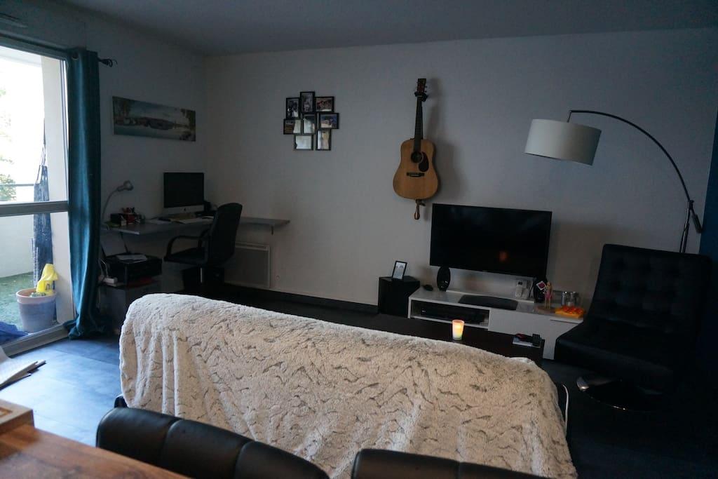 Salon avec TV, canapé, guitare et bureau.