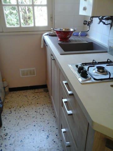 La cuisine équipée d'un four, de deux plaques et du matériel essentiel pour cuisiner.