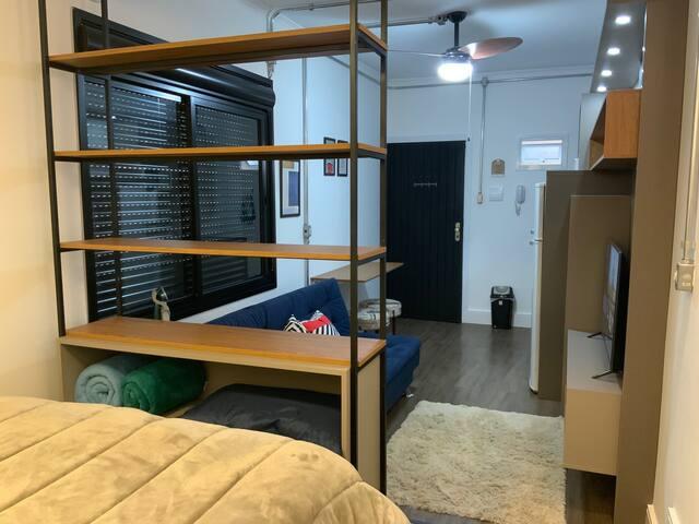 Dividindo os ambientes, uma estante moderna em ferro para você acomodar seus pertences.